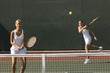 Doubles Player Hitting tennis ball with Forehand, team-mate standing at net