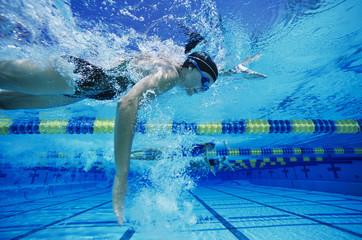 Female swimmer racing underwater in pool