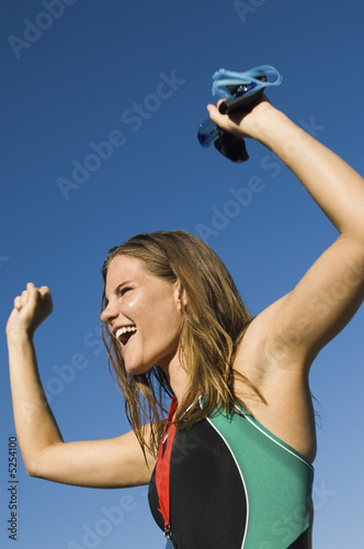 Female swimmer celebrating team-mates victory, low angle view
