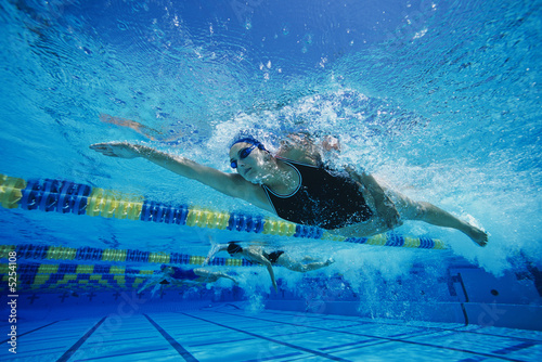 Female swimmers racing underwater in pool