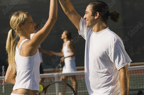 Mixed Doubles Partners High-Fiving Each Other on tennis court, side view
