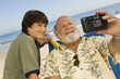 Boy and grandfather photographing themselves on beach
