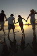 Family running through sea at sunset, back view, silhouette