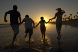 Family running through sea holding hands at sunset, back view, silhouette