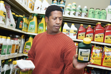Man selecting plant care products in shop