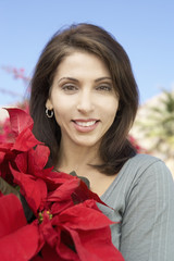 Woman with Poinsettia, outdoors, portrait