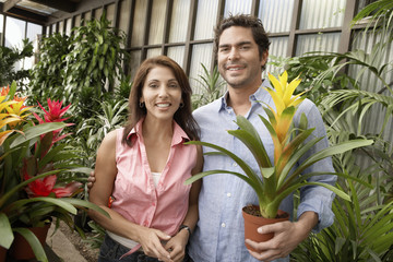 Couple at plant nursery, smiling, portrait