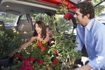 Couple loading plants into car