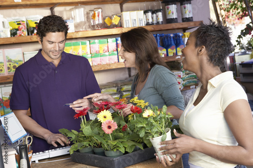 Friends purchasing plants in shop