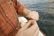 Fisherman baiting hook on boat, close-up