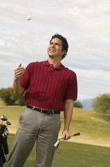 Golfer Holding Putter Tossing Golf Ball in Air on golf course