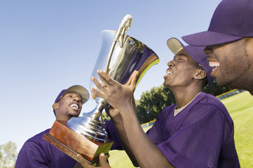 Baseball team mates with trophy, celebrating outdoors
