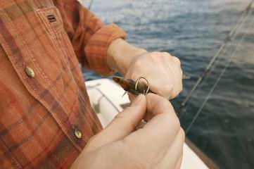 Fisherman baiting hook on boat, close-up