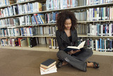 Young woman sitting on library floor, reading