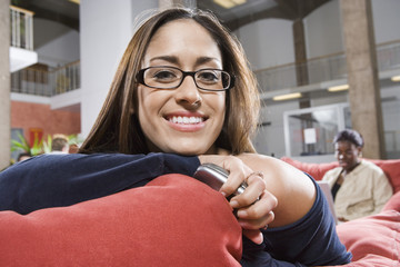 College girl student smiling, sitting on sofa in common room