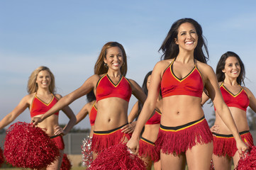 Cheerleaders doing routine with pom poms