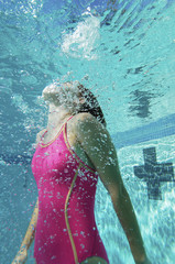 Female swimmer coming up for air, underwater