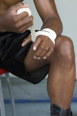 Boxer wrapping hands in tape, close up, mid section