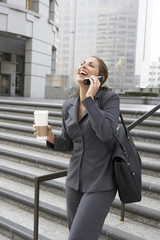 Businesswoman with Cell Phone and Coffee Cup