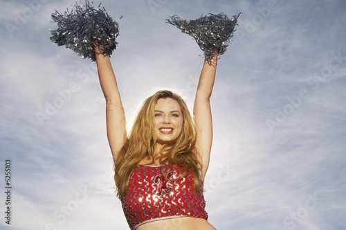 Cheerleader with pom poms raised, portrait