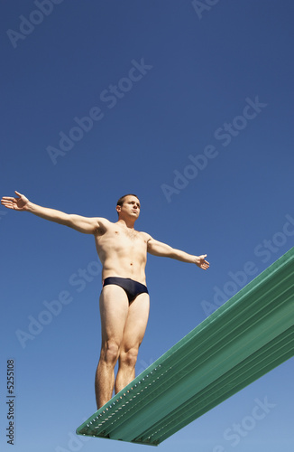 Man about to dive backwards off a diving board