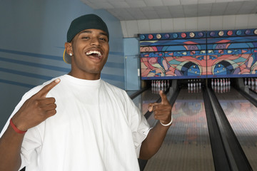 Young man at bowling alley celebrating, portrait