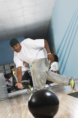 Young man releasing bowling ball, portrait