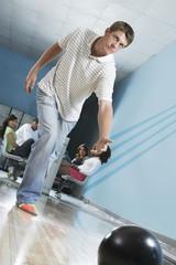 Young man releasing bowling ball, portrait