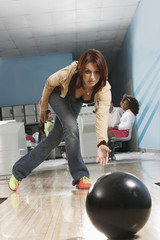 Young woman releasing bowling ball, portrait