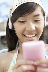 Young woman listing to mp3 player, head and shoulders