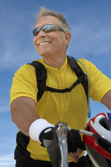 Man on bicycle ride, portrait, low angle view