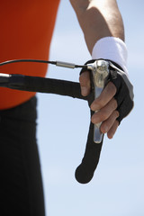 Man with hand on bicycle brake, close-up on hand
