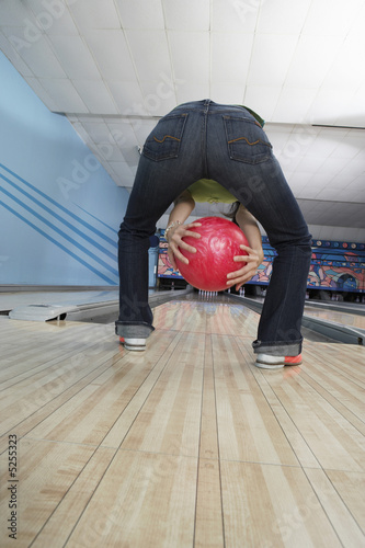 Young woman bowling, back view