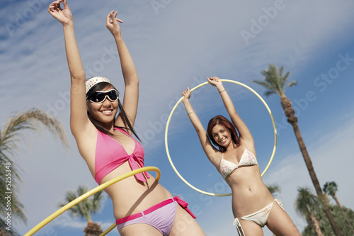 Young women in bikinis with hoops