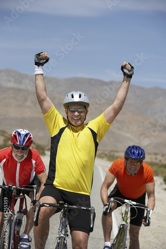 Cyclist cheering with raised arms, portrait