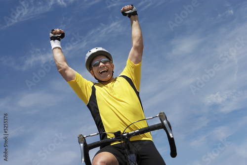 Cyclist riding bicycle and cheering, portrait, low angle view