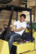 Man driving forklift in warehouse full of wood