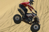 Quad bike rider in mid-air over sand, close-up