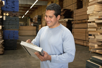 worker checking clipboard in warehouse of wood