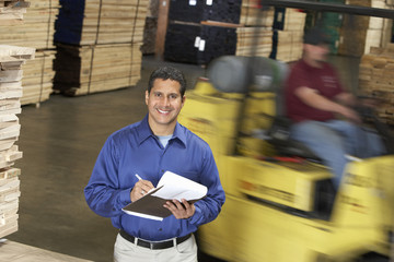 man with clipboard in front of forklift in warehouse