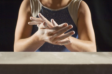 Gymnast 13-15 rubbing chalk into hands, mid section