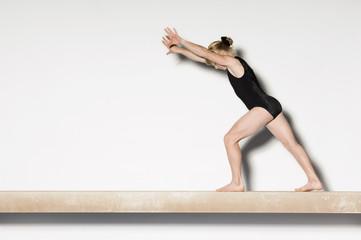 Gymnast13-15  on balance beam preparing to do handstand, side view