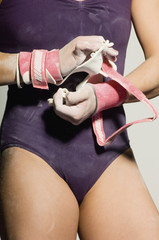 Gymnast 13-15 putting on palm guards, mid section