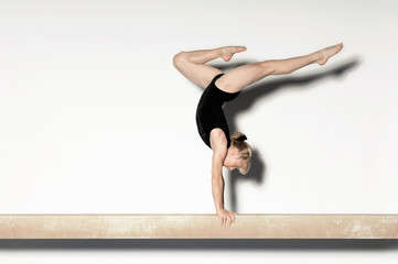 Gymnast 13-15 doing handstand on balance beam, side view