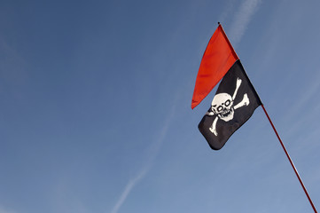 Skull and crossbones flag and red flag against blue sky