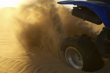 Quad bike spraying up sand in desert, close up