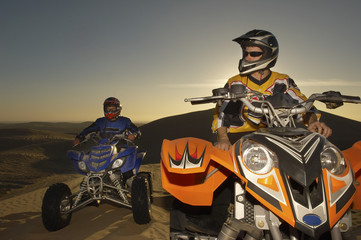 Men sitting on quad bikes in desert at sunset, close up