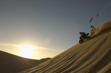 Men riding quad bikes in desert at sunset