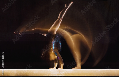 Multiple exposure image of female gymnast in motion on balance beam
