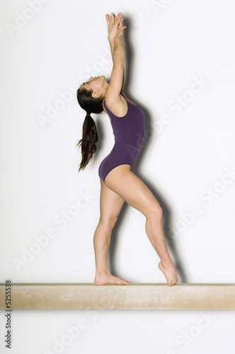 Gymnast 13-15 posing on balance beam, side view